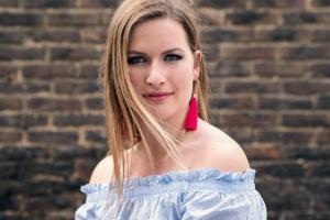 Porträt einer blonden Frau mit pinken Ohrringen