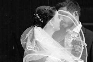 Porträt und Hochzeit, Hochzeitsfotografie eines Brautpaares mit wehendem Schleier